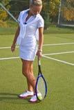 A menina feliz está com a raquete na corte no dia de verão ensolarado Imagem de Stock Royalty Free