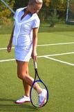 A menina feliz está com a raquete na corte no dia de verão ensolarado Fotos de Stock Royalty Free