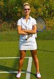 A menina feliz está com a raquete na corte no dia de verão ensolarado Fotografia de Stock
