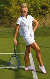 A menina feliz está com a raquete na corte no dia de verão ensolarado Fotografia de Stock Royalty Free