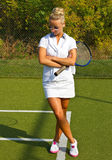 A menina feliz está com a raquete na corte no dia de verão ensolarado Foto de Stock Royalty Free