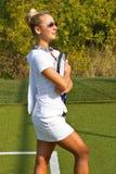 A menina feliz está com a raquete na corte no dia de verão ensolarado Imagens de Stock