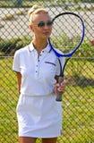 A menina feliz está com a raquete na corte no dia de verão ensolarado Foto de Stock
