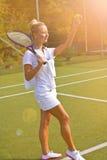 A menina feliz está com a raquete na corte no dia de verão ensolarado Imagem de Stock