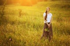 A menina feliz está com um ramalhete no meio do prado fotografia de stock royalty free