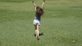 A menina feliz está correndo ao longo da grama verde no campo e está levantando as mãos Mulher bonita nova que movimenta-se e que vídeos de arquivo