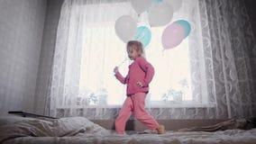 A menina feliz está correndo perto da janela na cama no berçário com o grupo de balões de ar em suas mãos e video estoque