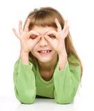 A menina feliz está mostrando o gesto dos vidros fotografia de stock