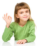 A menina feliz está mostrando o sinal APROVADO foto de stock