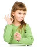 A menina feliz está mostrando o sinal APROVADO foto de stock royalty free
