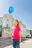 A menina feliz está na rua com balão azul Imagem de Stock Royalty Free