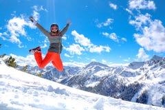 A menina feliz está saltando na neve nas montanhas fotografia de stock