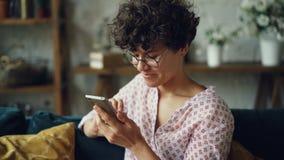 A menina feliz está usando o smartphone que olha a tela e rir amigos texting e verificação de meios sociais explica dentro vídeos de arquivo