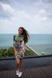A menina feliz, estando nos trópicos, é muitos mares, grama, árvores, foto morna, menina estar no mar, zhknshchina elegante foto de stock royalty free