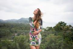 A menina feliz, estando nos trópicos, é muitos mares, grama, árvores, foto morna, menina estar no mar, zhknshchina elegante imagens de stock royalty free