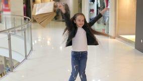 A menina feliz exulta a compra nova ao andar no shopping video estoque