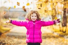A menina feliz joga as folhas de outono no ar Imagens de Stock