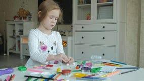 A menina feliz joga com plasticine, bolas de rolos com suas mãos, figuras e os lápis da cor encontram-se no desktop vídeos de arquivo