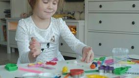 A menina feliz joga com plasticine, bolas de rolos com suas mãos, figuras e os lápis da cor encontram-se no desktop filme
