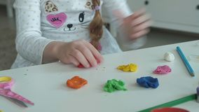 A menina feliz joga com plasticine colorido, esculpe uma figura, no desktop é figuras e lápis coloridos, video estoque