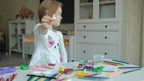 A menina feliz joga com plasticine, esculpe uma figura, no desktop é figuras e lápis coloridos, video estoque