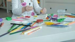 A menina feliz joga com plasticine, esculpe uma figura, no desktop é figuras e lápis coloridos, filme