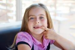 A menina feliz loura da criança que mostra a recortou os dentes Fotografia de Stock Royalty Free