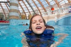 Menina feliz na água azul do colete salva-vidas na claro imagem de stock
