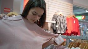 A menina feliz na compra, fêmea dos clientes novos escolhe a roupa nova na loja da forma durante descontos sazonais na alameda video estoque
