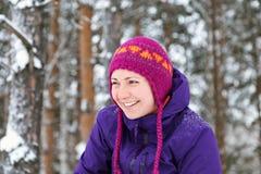 Menina feliz na floresta do inverno que joga na neve e nos sorrisos Imagem de Stock