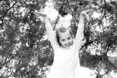 Menina feliz na pose do vestido da forma na árvore verde Sorriso da criança pequena com o cabelo louro longo exterior Modelo da c imagens de stock royalty free