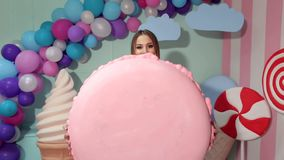 Menina feliz na roupa brilhante que realiza em sua mão um marshmallow enorme Menina dos doces filme