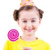 A menina feliz na terra arrendada do chapéu do partido coloriu doces Foto de Stock