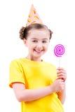 A menina feliz na terra arrendada do chapéu do partido coloriu doces Fotos de Stock