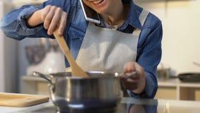 Menina feliz no avental que agita a sopa na bandeja com colher de madeira e que fala no telefone filme