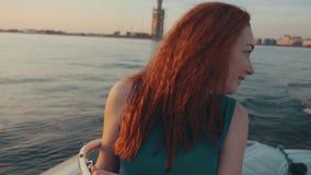 Menina feliz no barco de motor do boi do vestido de turquesa Noite do verão romântico Por do sol filme