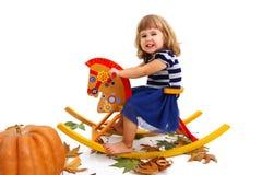 Menina feliz no cavalo de madeira isolado no fundo branco Foto de Stock Royalty Free