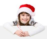 Menina feliz no chapéu de Santa com o bastão de doces do Natal que está atrás da placa branca Isolado no fundo branco Imagem de Stock Royalty Free