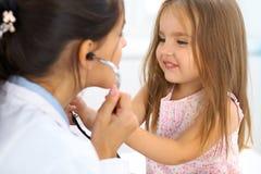 Menina feliz no exame da saúde no escritório do doutor Conceito da medicina e dos cuidados médicos Foto de Stock