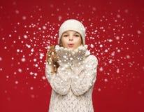 A menina feliz no inverno veste o sopro nas palmas fotografia de stock royalty free