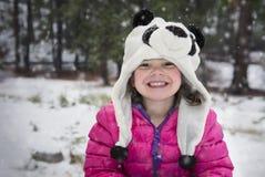 Menina feliz no revestimento cor-de-rosa da neve fotografia de stock royalty free