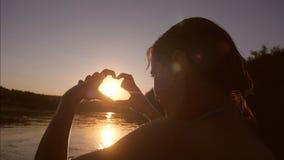 A menina feliz no rio mostra as mãos com forma do coração no por do sol, no fundo do rio menina bonita que banha-se no lago sobre vídeos de arquivo