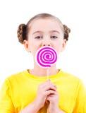 Menina feliz no t-shirt amarelo que come doces coloridos Fotografia de Stock Royalty Free