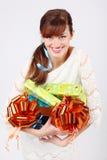 A menina feliz no vestido mostra caixas com presentes Foto de Stock