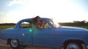 Menina feliz nos óculos de sol que inclinam-se fora da janela de carro retro e que apreciam a viagem Jovem mulher que olha para f video estoque