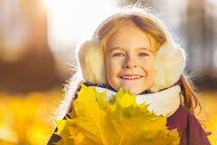 Menina feliz nos earflaps com folhas de outono Fotografia de Stock