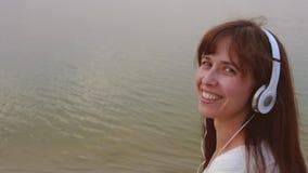 A menina feliz nos fones de ouvido mostra a língua e os sorrisos ao andar na praia filme