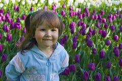 Menina feliz nos tulips Fotografia de Stock Royalty Free