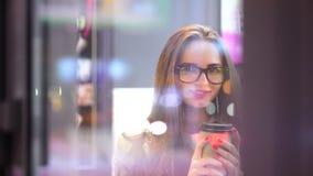 Menina feliz nos vidros que bebe o café ou o chá e que relaxa no café, sorrindo e olhando a câmera através de um café da janela filme