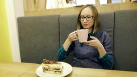 Menina feliz nos vidros que bebe o chá quente com mirtilos e hortelã de um copo cor-de-rosa grande e que relaxa no café, sorrindo vídeos de arquivo